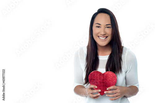 Smiling young woman hold red heart