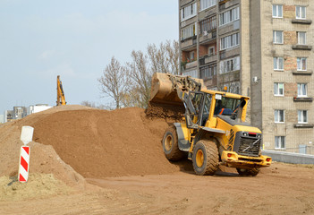 The wheel loader forms a sandy embankment