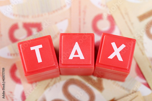 Tax word on money background