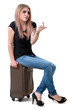 Picture of lovely woman sitting on suitcase