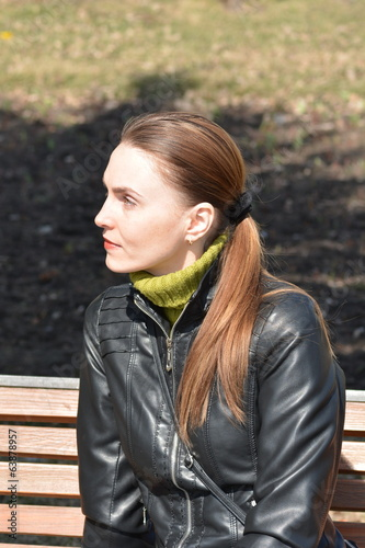 Woman sitting on a bench in a sunny day