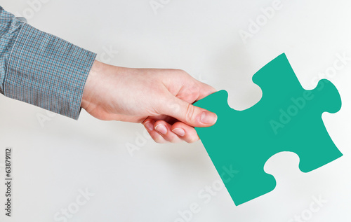 female hand holding green puzzle piece