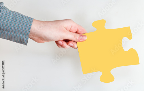 female hand holding yellow puzzle piece