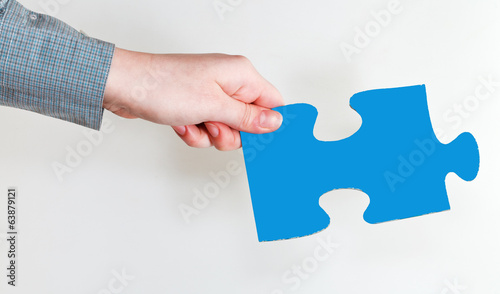 female hand holding blue puzzle piece