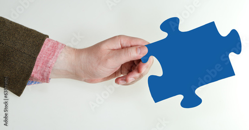 male hand holding blue puzzle piece