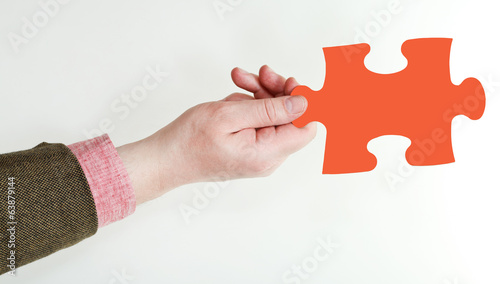 male hand holding red puzzle piece
