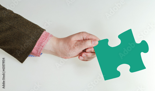 male hand holding green puzzle piece