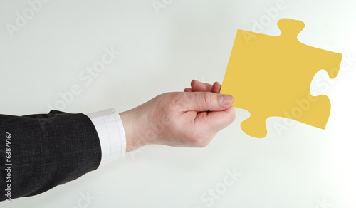 male hand holding yellow puzzle piece