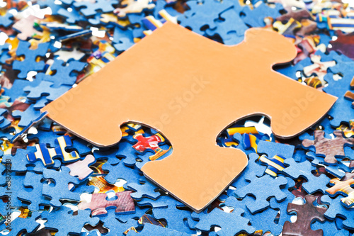 separated piece on pile of disassembled puzzles