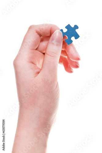 female hand keeps jigsaw puzzle piece