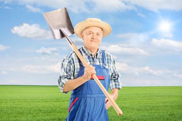 Mature agricultural worker holding shovel
