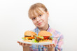 Little smiling blond girl with homemade hamburgers on white plat