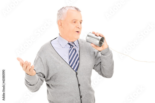 Senior man talking through a tin can phone