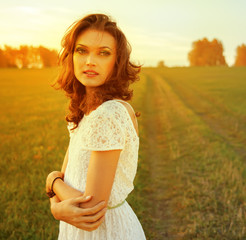 Beautiful brunette woman in field at sunset
