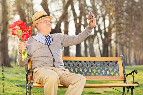 Senior taking selfie with cell phone in park