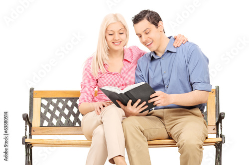 Young couple reading a book seated on bench