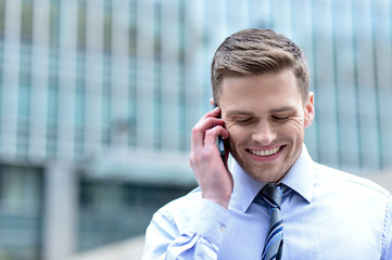 Smiling corporate guy talking on the phone