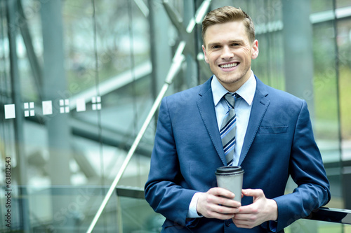 Smiling businessman with cup of a coffee