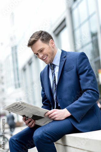 Smiling businessman reading paper at outdoors