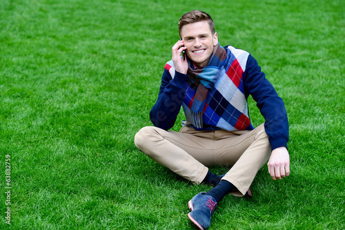 Happy young man communicating, posing outdoors