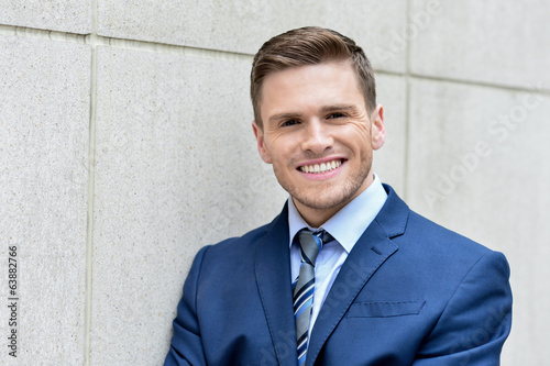 Businessman leaning against a concrete wall
