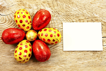 Colorful chocolate Easter eggs in foil on wooden background