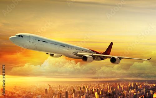 Fototapeta Airplane flying above city at sunset