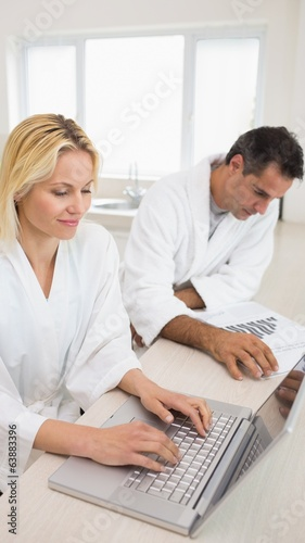 Couple with bills and laptop in the kitchen