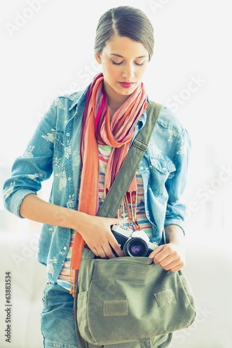 Young pretty woman taking camera from her bag