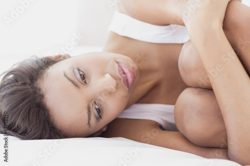 Unhappy brunette lying on bed hugging her knees