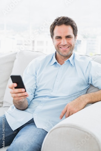 Smiling man sitting on the couch sending a text with smartphone