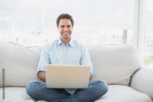 Happy man using laptop smiling at camera sitting on sofa