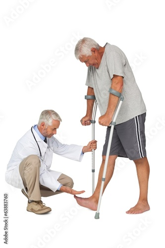 Side view of a doctor with senior man using walker