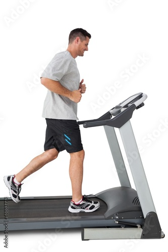 Full length of a young man running on a treadmill
