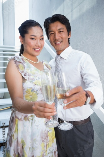 Happy couple dressed up for a date having champagne