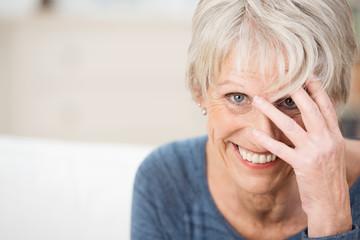 lächelnde seniorin fasst sich an den kopf