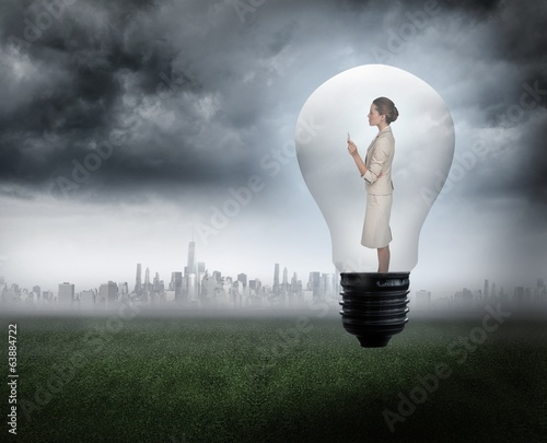 Composite image of thinking businesswoman in light bulb