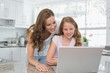 Happy mother and daughter using laptop in kitchen