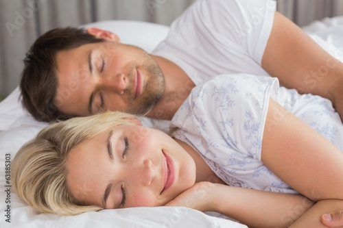 Couple lying in bed with eyes closed