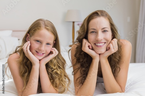 Smiling mother and daughter lying in bed