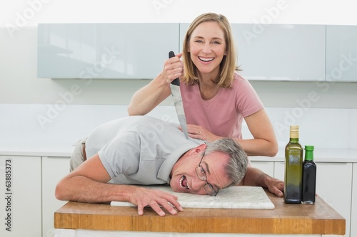 Happy woman holding knife to man's neck in kitchen