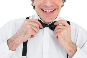 Smiling groom adjusting bow tie