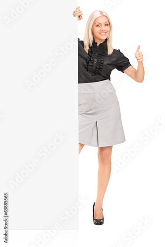 Woman standing behind panel and giving thumb up