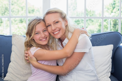 Happy mother and daughter embracing on sofa