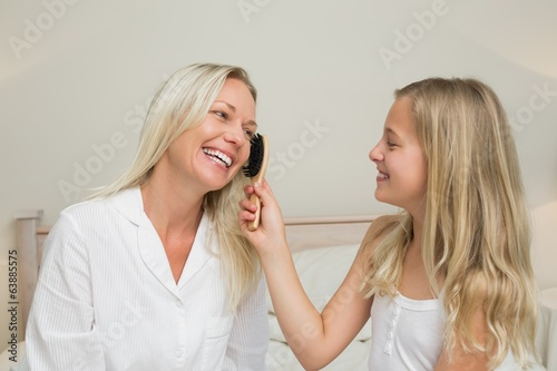 Girl brushing hair of mother in bedroom