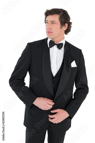 Thoughtful groom in tuxedo getting ready