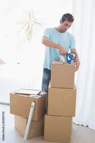 Man with cardboard boxes in new house
