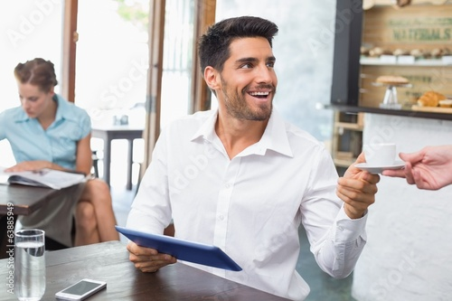 Man receiving coffee while using digital tablet in coffee shop