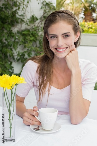 Smiling young woman with coffee cup in café