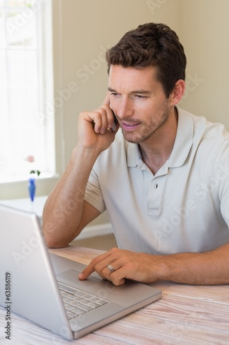 Man using laptop and mobile phone at home
